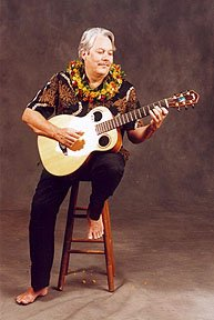 A picture of Keola playing the guitar, seated on a stool